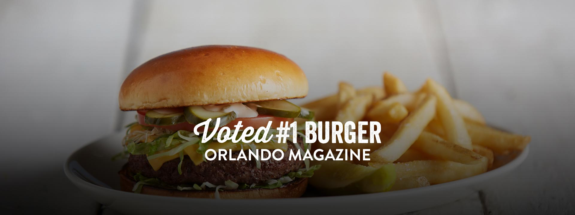 Hamburger and french fries with text: Voted 1 burger, Orlando magazine