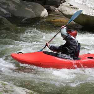 man rafts a red kayak
