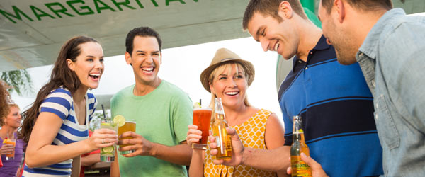 Two girls and three men on vacation drink drinks