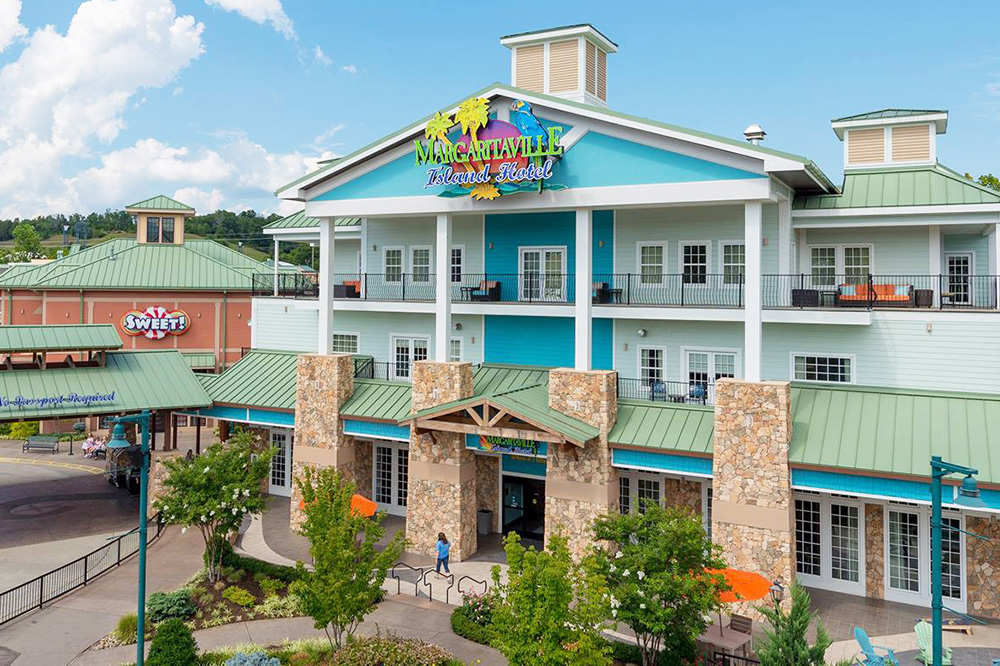 image of the Island Hotel exterior, drenched in sunlight featuring lime greem metal rooftops, turquoise colored accent sideing, with entryway surrounded by tall white pillars and stacked brown stone bases.
