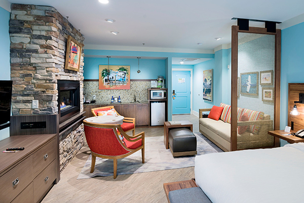 image of the hotel king deluse room featuring seafoam blue color walls, brown stone stacked fireplace, coformatable sitting chairs facing a large couch with island-inspired fabrics and colored pillows.