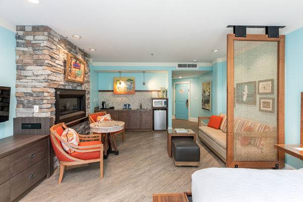 Image of a deluxe guest room with turquoise painted walls, a main sitting room with orange chairs and comfortable sofa facing a wall with fireplace inset.