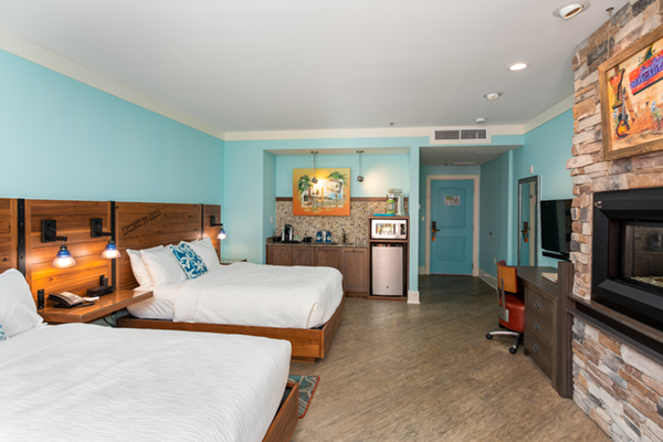 Image of a two bedroom guest room with turquoise painted walls, two queen-sized beds facing a wall with fireplace inset.