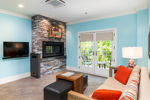 Image of a one bedroom guest room with turquoise painted walls, sitting room with sofa and cocktail table facing a wall with fireplace inset.