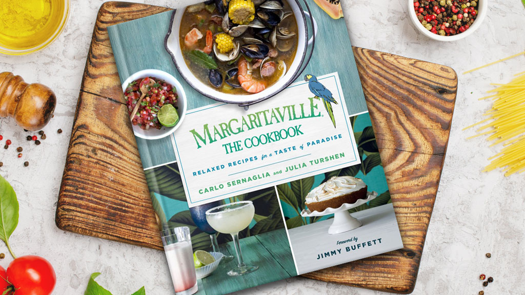 Margaritaville Cookbook lying on a cutting board on a table of food