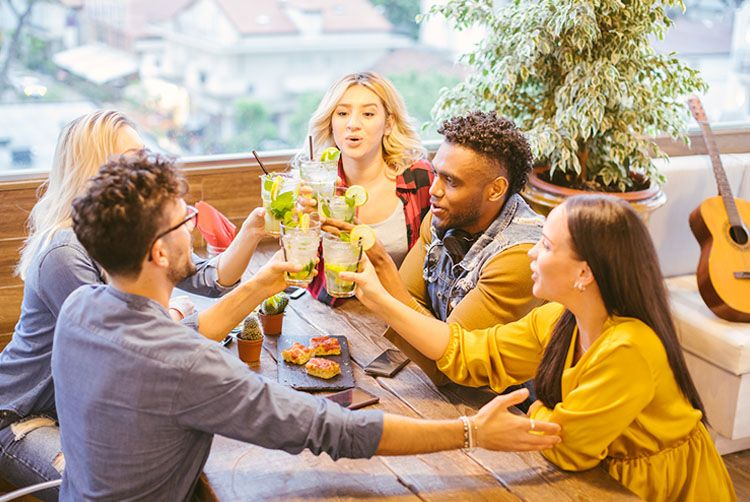 People sitting around a table with drinks - celebrate your birthday or milestone at Margaritaville Hotel Nashville with the Growing Older But Not Up offer