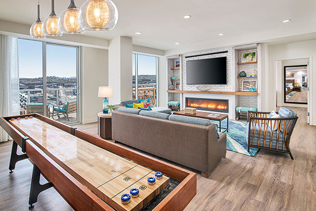 A room with seating area, shuffleboard table, and large glass window with view of city