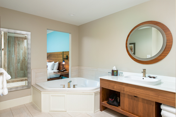 Image of the whirlpool tub and vanity on white tiles and window cut-out to suite sitting room.