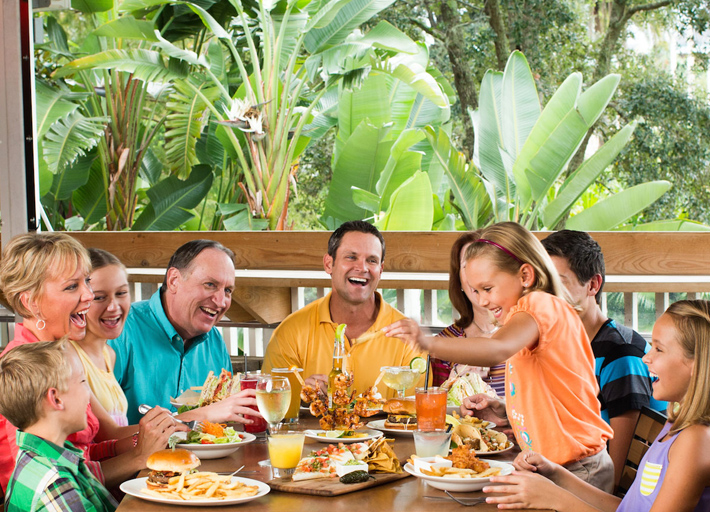 A large family gathered around an outdoor table with food and drinks laughing and having a good time