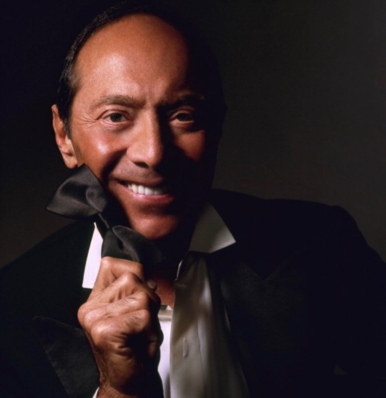 Image of a smiling Paul Anka wearing a tuxcedo with open collar holding a black bow tie