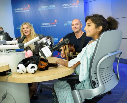 SeacrestStudios(D151005R): Taylor Sanders (Patient, 11 y/o, hospital gown, far right) knows the words to one of Kelsea's songs and sings along in Seacrest Studios.  Kelsea Ballerini (Country Music Performer) visited Seacrest Studios with members from her live band to chat with patients and play some of her songs.