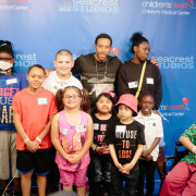 Ludacris (rapper and movie star) visits with patients and siblings at the Seacrest Studio's Red Balloon Network at Children's Medical Center Dallas while he was in town. Photographer here Yahaira Barnett (girl on left with mask), Kaden Lee age 12 (patient in orange shirt) Jorge R (sibling in white shirt), Abygail R (girl in pink shirt and glasses), Allison Fuentes age 6 (patient black and pink shirt) Ludacris (black shirt adult rapper and movie star), Dominic Ayala age 6 (sibling with hat), Akeela Coakley (sibling white shirt), Genesis Coakley (black sweat shirt) and Isaiah Cervantes (patient in wheel chair).