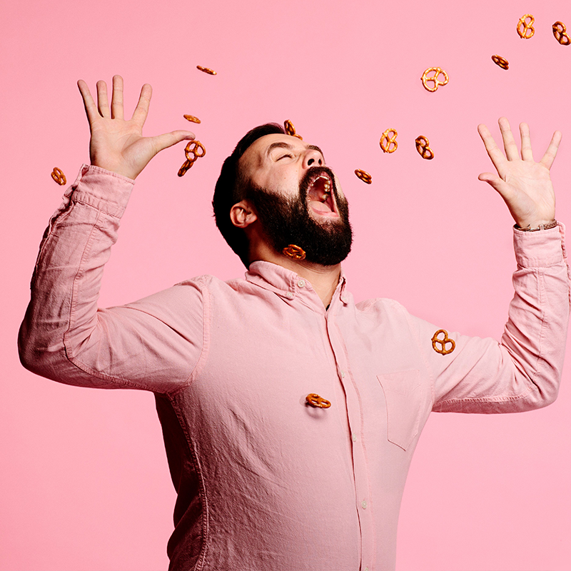 image of a man wearing a pink long sleeve shirt opening his mouth to catch flying pretzels coming at him