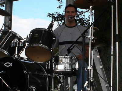 Mike trying to smile, sing AND drum!