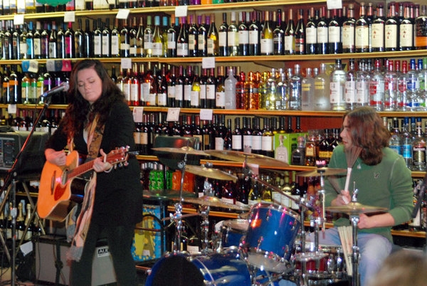 Kelly Carvin and her drummer share a song and look at all the liquor.