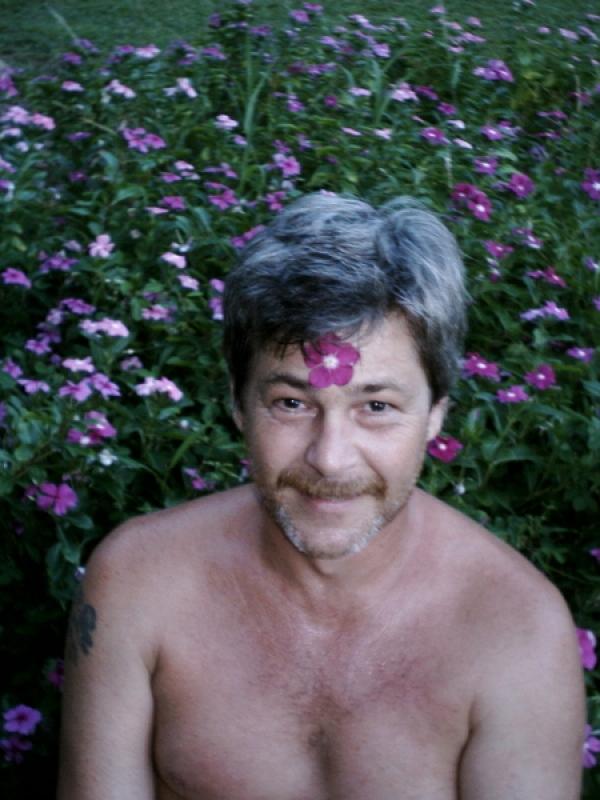 Sitting in the flowers, with one glued to my forehead with sap (Wild Vinca). Honomu, Hamakua, Big Island, Hawai'i. (2004)