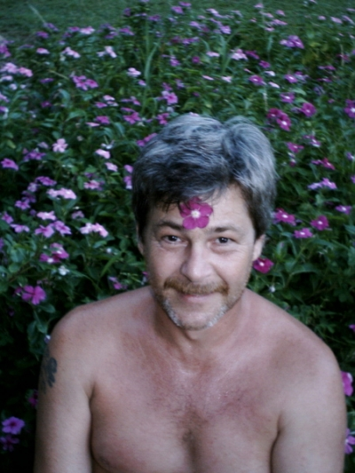 Sitting in the flowers, with one glued to my forehead with sap (Wild Vinca). Honomu, Hamakua, Big Island, Hawai'i. (2004)