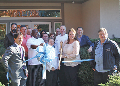 A ribbon-cutting was held Dec. 18 for SERG Catering and Special Events, the latest addition to the Southeastern Restaurant Group enterprise. Director of sales Molly Kennedy holds the scissors, joined by Chef Andy Borgmeier to her right, while Chef Milton