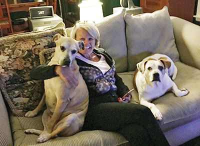 Palmetto Animal League volunteer Terry Bergeron relaxes at home with her two rescue dogs, Molly and Lucy. Bergeron offers her media and marketing expertise pro bono as a way to support PAL. MICHAEL WEAVER
