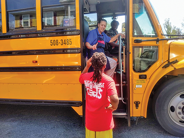 Teresa Arnold, an employee of Sodexo, takes a lunch request from a student March 19 in the parking lot of Hallmark Homes at Malphrus in Bluffton. Bus driver Ethel Mitchell said they had handed out 160 breakfasts and 266 lunches that day. Since then, the d