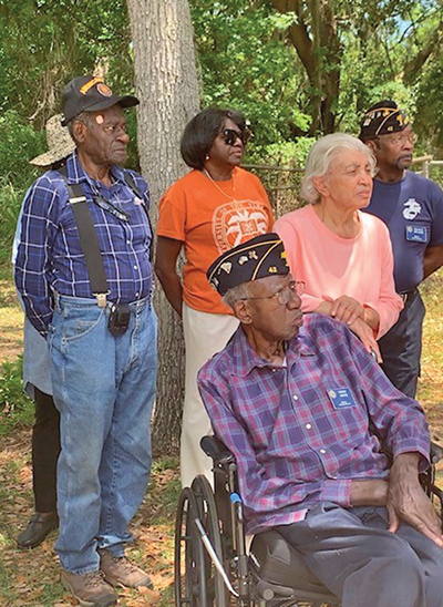 Perry White, seated, is joined by family and friends as he surveys the work being done on his home by L3 Kigre and the American Legion Post 42 of Hilton Head Island. COURTESY BCEDC