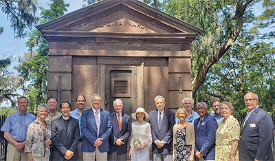Island dignitaries gather in front of Baynard Mausoleum May 6 to commemorate the Zion Chapel of Ease Cemetery being recognized on the National Register of Historic Places. Iva Welton, center, a member of the Board of Directors of the Heritage Library, hol