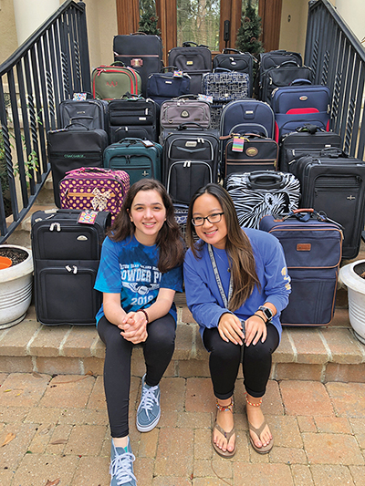 Anna Borelli, left and Liana Hutton with the two dozen suitcase they collected, cleaned, filled and donated to CAPA's Open Arms Children's Home. SUBMITTED