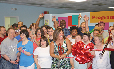Staff, members, families and supporters of Programs for Exceptional People (PEP) gathered July 24 for a ribbon cutting and celebration of the completion of the organization's new location in Bluffton's Sheridan Park. Marielena DiMatteo, center, holding th