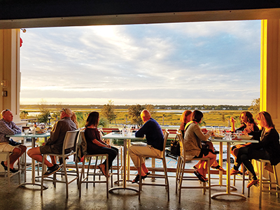 Customers at Poseidon, one of the SERG family of restaurants, enjoy a sunset over Broad Creek from the top floor of the establishment. COURTESY SERG