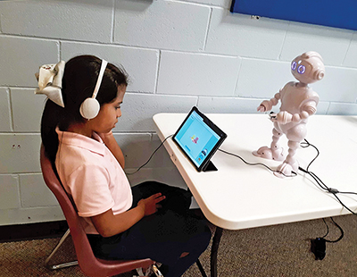 Allison Castillo, 8, a member of the Boys & Girls Club of Hilton Head Island, works on a math game with one of the ABii learning robots recently brought to the club. AMY COYNE BREDESON
