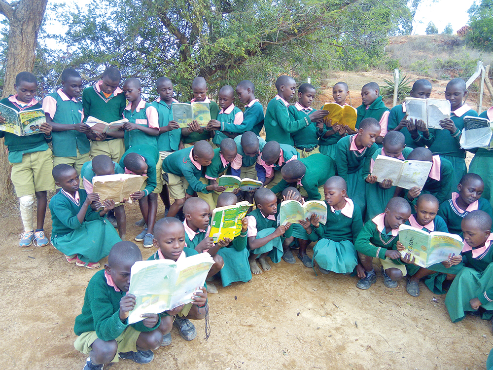 Students at the Kyalinlini School in Kitui, Kenya, share books received from Libraries for Kids International, a nonprofit based in Bluffton. COURTESY LIBRARIES FOR KIDS