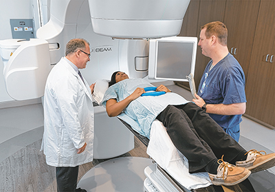 Dr. Jonathan Briggs, medical director for radiation oncology services, and Ryan Grove, chief radiation therapist, treat a patient using the  state-of-the-art TrueBeam radiotherapy system at the new Keyserling Cancer Center. COURTESY BEAUFORT MEMORIAL HOSP