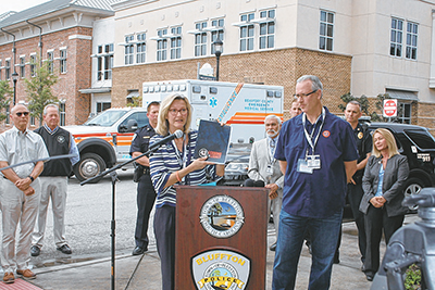 At a press conference April 9, Bluffton Mayor Lisa Sulka shows a Lutzie 43 Foundation leadership manual as Mike Lutzenkirchen, founder of the organization, listens. Also attending were members of Bluffton Town Council, Bluffton Police Chief Chris Chapmond