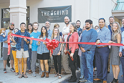 The Grind Coffee Roasters celebrated the opening of its coffee shop in a new space with a ribbon cutting April 17, assisted by the Greater Bluffton Chamber of Commerce. In the photo, Ian and Kathleen Duncan hold the scissors while staffers and friends, al