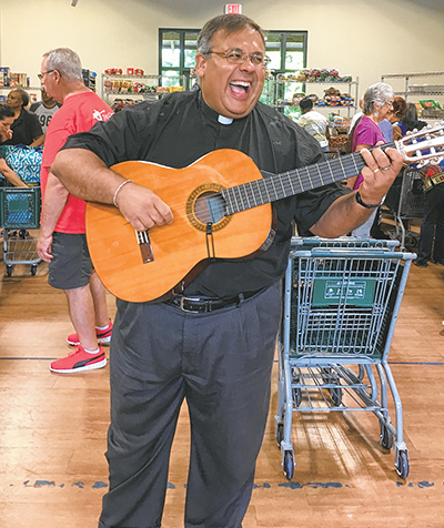 Rev. Juan Rivera plays his guitar and sings for volunteers and patrons at the Church of the Cross weekly food bank. EDWINA HOYLE