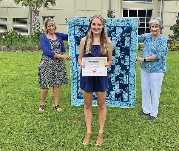 Molly Rembold, a 2020 graduate of John Paul II Catholic School, received a scholarship and a handmade quilt from Palmetto Quilt Guild June 17. Also pictured are Lisa Jacobsen, left, and Cindy Strickland, members of the Guild.