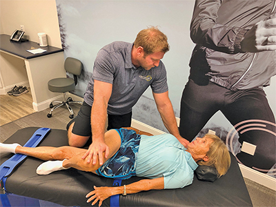 Stretch Zone manager Jay Goodwin illustrates the benefits of stretching to Dr. Jean Harris. LYNLY TRIGG