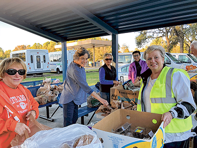 In this photo from November 2017, Fill the Need project coordinator Margie Tomczak, right, leads volunteers in packaging bags for bus riders. FILE PHOTO