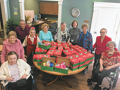 A group of residents at Palmettos Assisted Living in Bluffton pose with the boxes they filled for Operation Christmas Child, an annual ministry project of Samaritan's Purse. COURTESY PALMETTOS ASSISTED LIVING