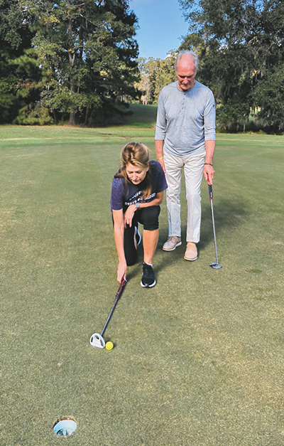Kimberly and Roger Jackson work on three-foot putts by playing a pull back putting game.  JEAN HARRIS