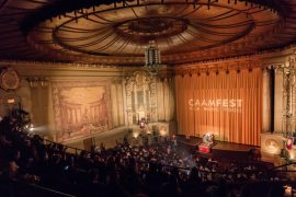 "A half-darkened theater, the historic Castro Theater in San Francisco, is filled with audience members waiting for a show to start. Dramatic lighting shines brightly on the curtain, with the words ""CAAMFest"" on the curtain."