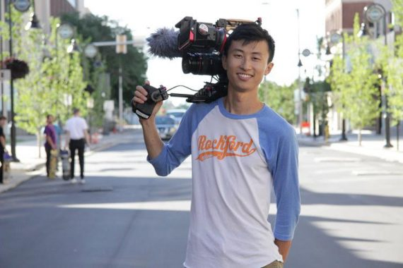 A young Asian American man smiles holding a video camera over his right shoulder.