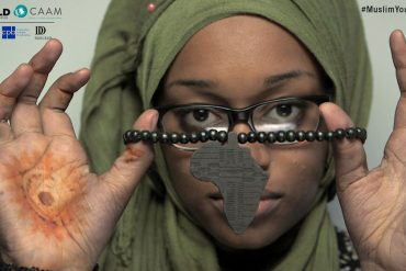 Close up photo of a young African American woman wearing a green head scarf holding a beaded bracelet in front of her. Her hands can be seen and the bracelet also has a pendant in the shape of Africa. The woman is wearing black-rimmed glasses and has a serious expression. Logos for Center for Asian American Media, WORLD Channel, Corporation for Public Broadcasting, and Doris Duke Foundation for Islamic Arts appears together in a corner.