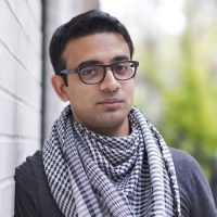 A South Asian young man with short brown hair, black wire rimmed glasses, and a black and white checkered scarf stands in front of a wall for his headshot.