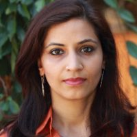 A South Asian woman with long reddish dark brown hair looks directly at the camera for her headshot with a serious face.