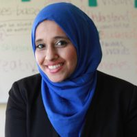 A smiling woman looks at the camera. She is wearing a bright blue headscarf and black blazer suit. Marya Bangee is the Executive Director of Harness.