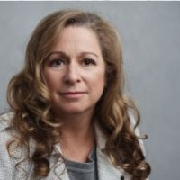 A white woman looks directly at the camera in her headshot. She is wearing a white blazer and grey shirt, and has curly blonde and brown hair. Abigail Disney is founder of Level Forward.
