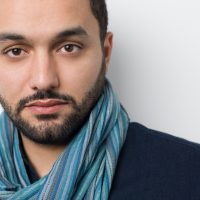 "A man with short hair and short beard looks at the camera for his headshot. He is wearing a teal scarf. Karim Amer is the director of Oscar-nominated ""The Square."""