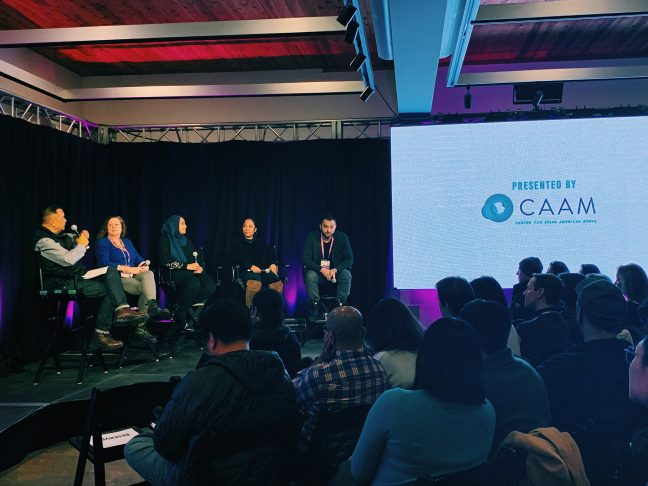 "Five people sit on stage on the left side of the photo; the CAAM logo is displayed on the screen on the right. Panelists at CAAM's Sundance 2019 panel, ""The Road to Decolonization."" Photo by Sapana Sakya."