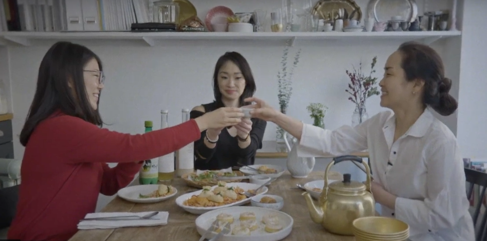 Three Asian women toast each other at a dining table.